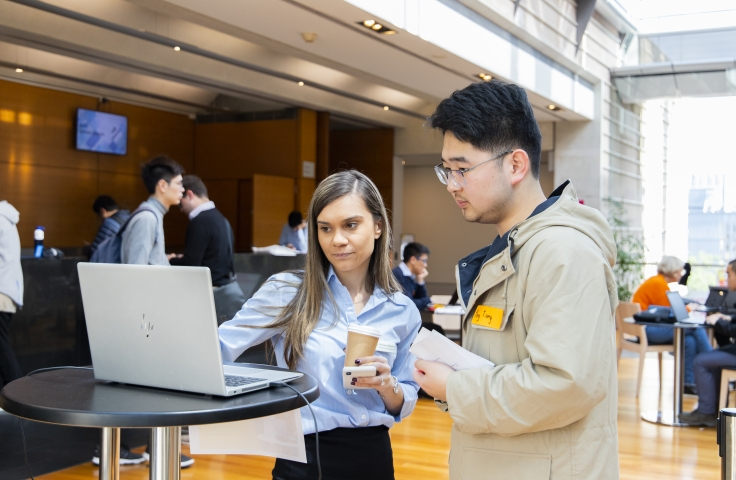 Image of staff memeber and student infront of a laptop